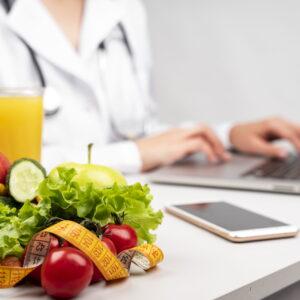 owoce laptop na drugim planie kobieta w kitlu pisząca na laptopie