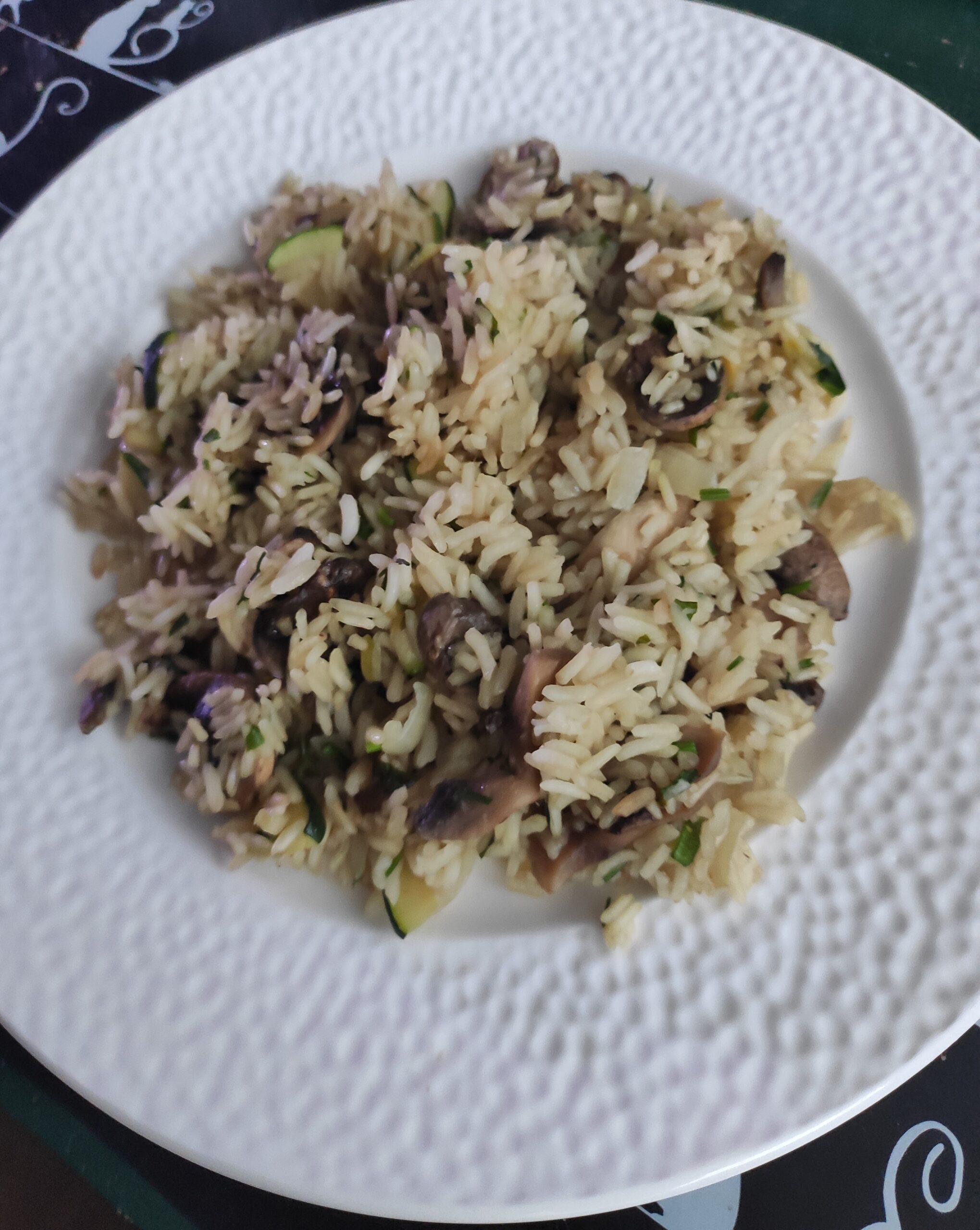 risotto z pieczarkami i cukinią podane na białym talerzu