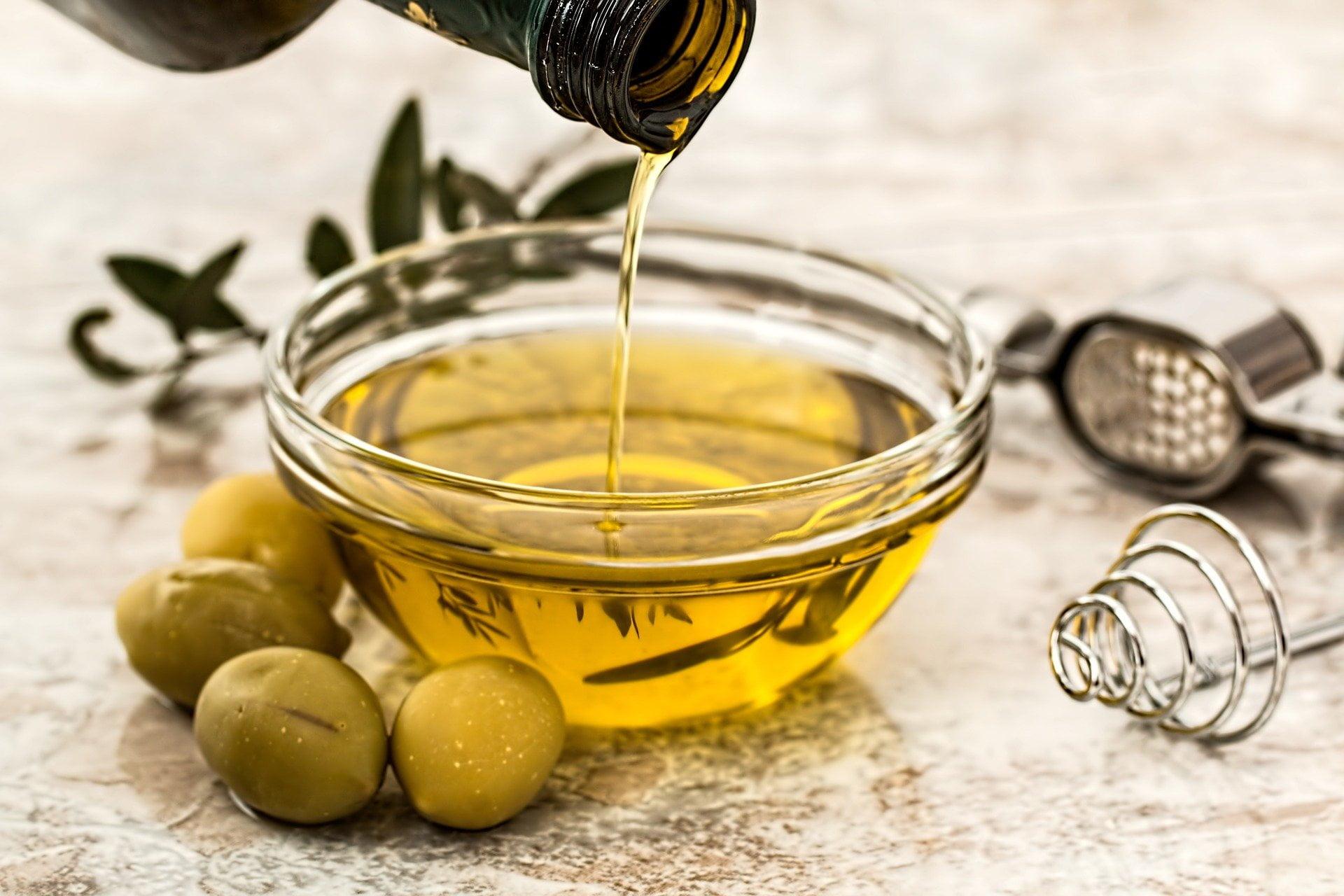 zielone oliwki, oliwa z oliwek wlewana do szklanej miski